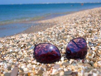 7502816-sunglasses-lying-on-a-summer-stony-beach-evpatoria-crimea-ukraine.jpg